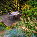 Deck with table and chairs in summer-dry garden.